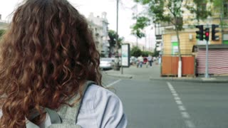 Slender woman with curly hair waiting for the green light on the sidewalk and crossing the road