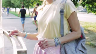 Slender young girl in bright summer clothes buys a bottle of water outdoors, slow motion