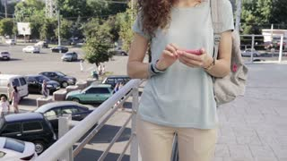 Slender young girl uses a pink mobile phone on city background in slow motion. Woman in a T-shirt with a backpack in the city in the summer.