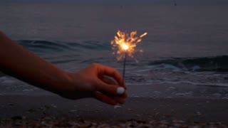 Sparkler burns in the sand on the beach on sea background