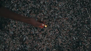 Top view of a woman lights a sparkler on the beach at night