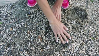 Top view of female hands find the stone on the shore among the sea shells and pick up it