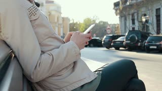 Mobile phone in female hands against city background