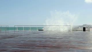 Sea waves breaking on the promenade