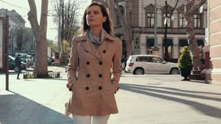 Slender girl in a beige coat and jeans