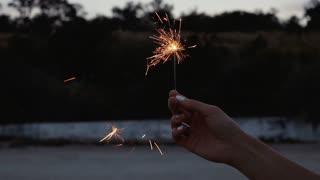 Sparkler in a female hand with white manicure in the evening on the beach, close-up