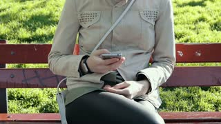 Woman in a beige jacket sits on a bench in the park and uses a mobile phone