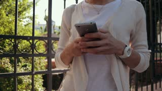Woman in white clothes is holding a mobile phone