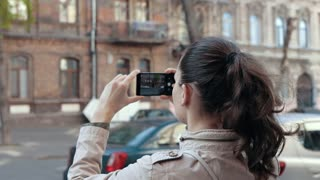 Woman tourist taking pictures of old architecture