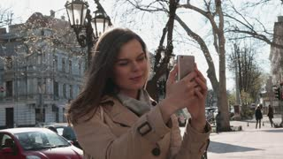 Young woman in a coat takes pictures of herself