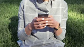 Young woman in gray sweater is holding a mobile phone in hands with white manicure on a background of a green lawn in the spring