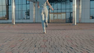 Young woman in jeans and a t-shirt joyously jumping outdoors