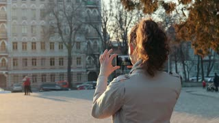 Young woman tourist in a beige jacket takes pictures of an old city in sunlight