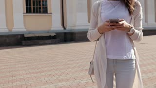 Young woman using a mobile phone in the city in summer