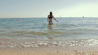 Young woman walks into the cold water on the beach