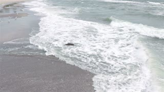 Waves cover the stone on beach in cloudy weather, slow motion, wide shot