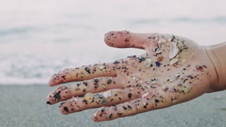 Wet female hand with seashells on the palm on sea background