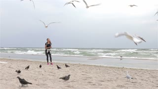 Woman feeding birds at the beach on a cloudy day, slow motion, wide shot