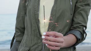Woman holding Sparkler in hand on beach, close-up