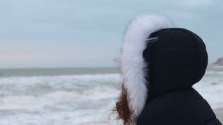 Woman in winter coat with hood looking at the sea before dawn