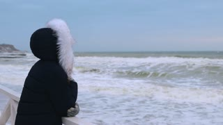Woman in winter coat with hood looking at the sea before sunrise