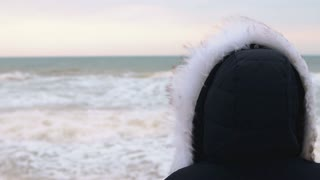 Woman in winter jacket with hood looking at the sea before sunrise