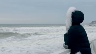 Woman in winter jacket with hood looking at the waves of the sea before dawn