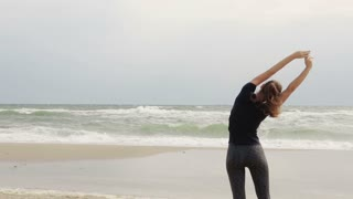 Young athletic woman doing exercises on the beach on a windy day against the sea, slow motion, wide shot, blur at the end