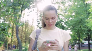Young attractive woman uses a smart phone in summer park, looking at the camera and smiling, lens flare
