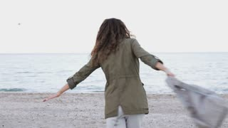 Young brunette in a green jacket and with backpack is happy on the beach