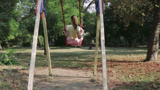 Young brunette rides a swing in the park in the summer, view from the back, slow motion. She is wearing a pink skirt and a yellow T-shirt.