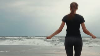 Young brunette with a skipping rope in the early morning on the beach