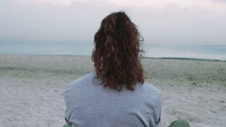 Young brunette with curly hair listening to music on the beach in the evening, view from the back, slow motion, the camera switches to a view of the sea