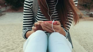 Young brunette woman in striped T-shirt sitting in the summer on the beach and listening to music