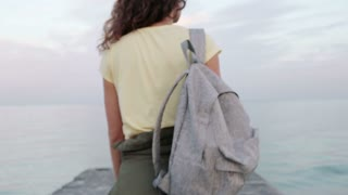 Young curly brunette in a yellow T-shirt with a backpack walking along the pier, stops at the edge and looks at the sea