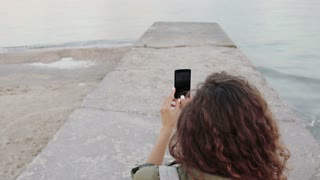 Young curly brunette shoots seascape on a mobile phone