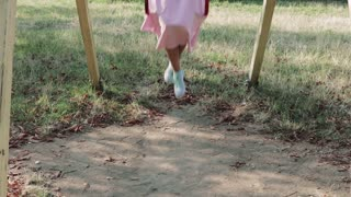 Young girl in pink skirt rides on a swing in the park in the summer, slow motion