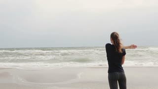 Young sporty woman doing exercises on the beach on a windy day against the sea, slow motion, wide shot, view from the back