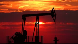 Oil pump jack against red sunset