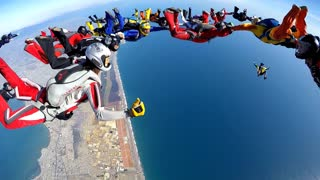 Group of skydivers are hovering in accelerated free fall above coastal city