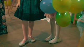 Two little girls with air  baloons dancing