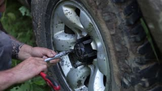 An man is screwing bolts on the wheel of a car