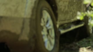 Dirty and mud-splattered car gets stuck in the mud on a bad dirt-road. Camera shoots from a close wheel angle.
