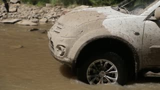 Dirty and mud-splattered white car crosses a river and travels on river stones. Camera shoots from a close wheel angle.