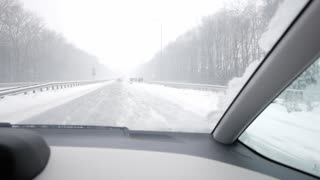 Driver's POV of driving on a highway on a winter day past a car crash site