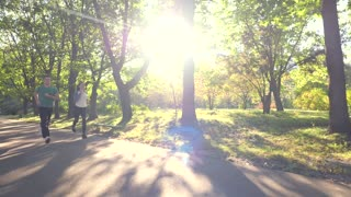 Young couple is running through the park on a sunny summer day, slow motion, view from the back, view in profile, tracking shot
