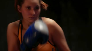 Young woman mma fighter training punches with hands on boxing gloves in air
