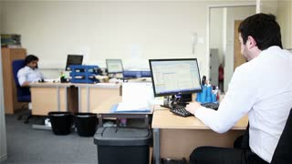 A candid real-world office scene with a pair of relaxed office workers. A female colleague walks into the scene to retrieve something from her desk before leaving again.