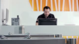 A receptionist sits in the background blur looking down at his computer.  Some clients leave the building and he bids them farewell.