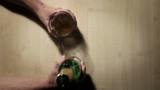 Abstract, top down view of a pair of anonymous hands pouring a glass of beer from the bottle; after a quick drink, the glass is returned to the table.